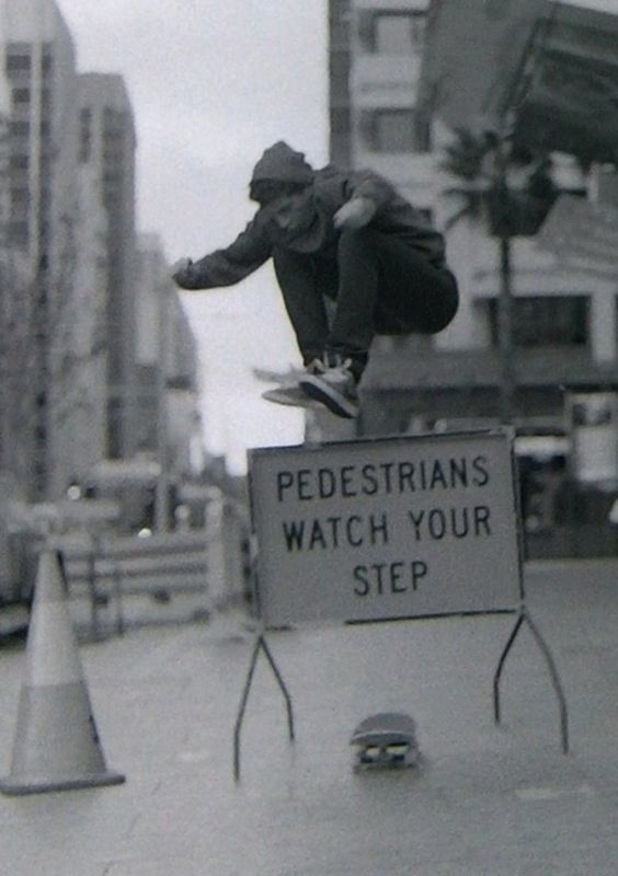 Skateboarder jumping Pedestrians watch your step sign.