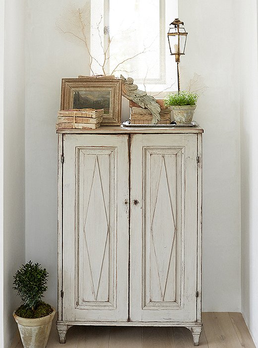 Swedish antique painted cabinet at #PatinaFarm with vellum books, antique painting, and #farmhousestyle home decor