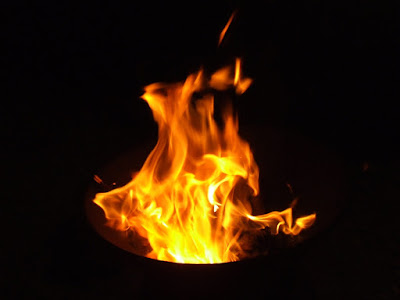 ID: against the black of night, the yellow and orange flames of a fire are visible moving and breathing with the wind.