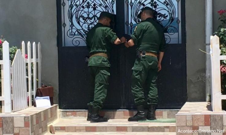 Policías cerrando iglesia en Argelia