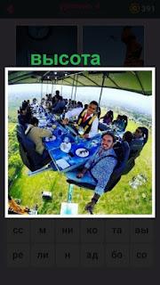 на большой высоте за столиками едят посетители в воздухе