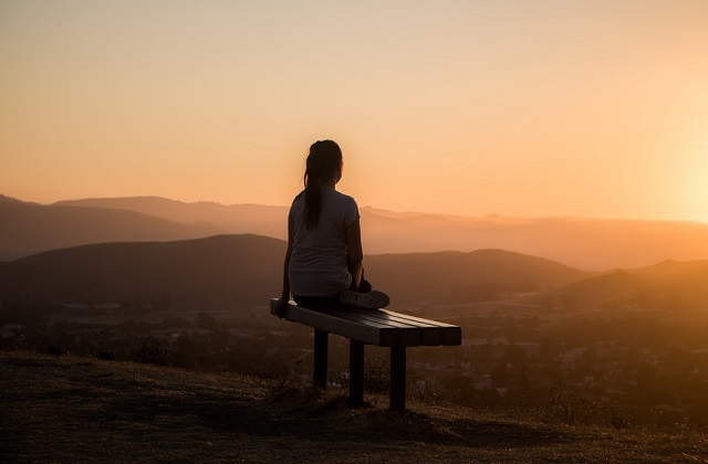woman sitting on a bench watching sunrise