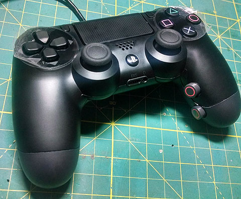 PS4 controller adapted for accessibility with grip mounted buttons.