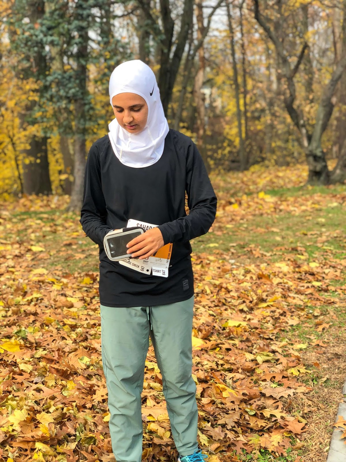 sahara with white nike hijab, black nike long sleeve and green running pants standing with her phone armband