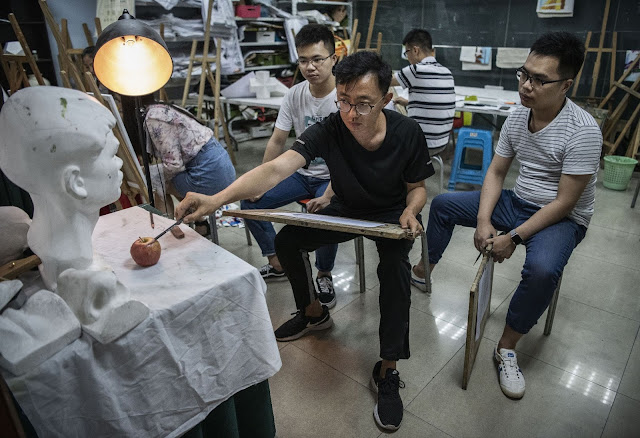 Huawei employees take part in an art class at a recreation area in staff housing at the end of the work day at the Bantian campus