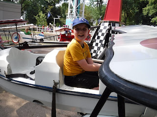 a boy in a yellow shirt and blue baseball cap sits in a white airplane ride at Adventureland Park in Altoona, Iowa