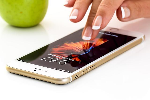 dedos de uma mulher desbloqueando um i phone 10