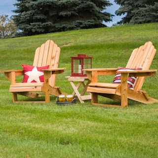Two Adirondack chairs with a red lantern on table between them. They also have two beers on a tray between them.