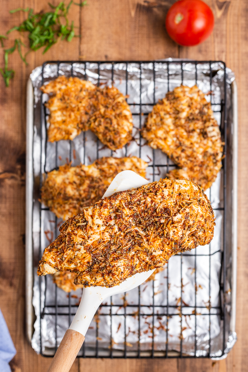 Overhead photo of cooked Keto Parmesan Chicken Cutlets on a sheet pan with one cutlet on a spatula closer to the camera.