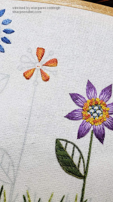 Third flower motif being embroidered in oranges