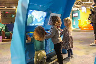 three small children play with an interactive exhibit; two screens are visible on a colorful blue curved background that extends above their heads, at the Kirby Science Discovery Center in Sioux Falls, South Dakota