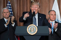 U.S. President Donald Trump speaks between Vice President Mike Pence (L) and EPA Administrator Scott Pruitt prior to signing an executive order on ''Energy Independence,'' eliminating Obama-era climate change regulations, during an event at the EPA (Credit: Reuters/Carlos Barria) Click to Enlarge.