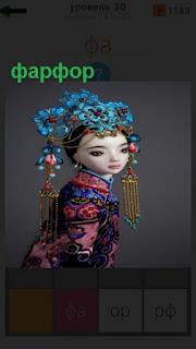 стоит кукла сделанная из фарфора, украшена бижутерией