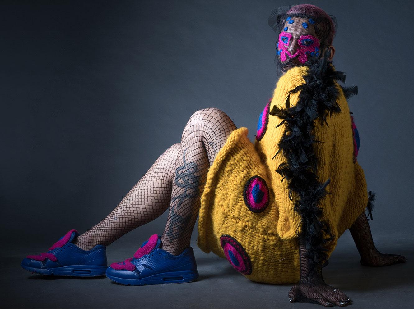 trabajo de alumna Paloma Tapia en Taller Vertical en Textil e Indumentaria UDP chaleco largo lana amarillo con plumas negras en brazos y círculos fucsia y azul