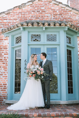 bride and groom in front of casa feliz blue window