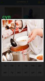 Повар разливает приготовленный суп по тарелкам половником