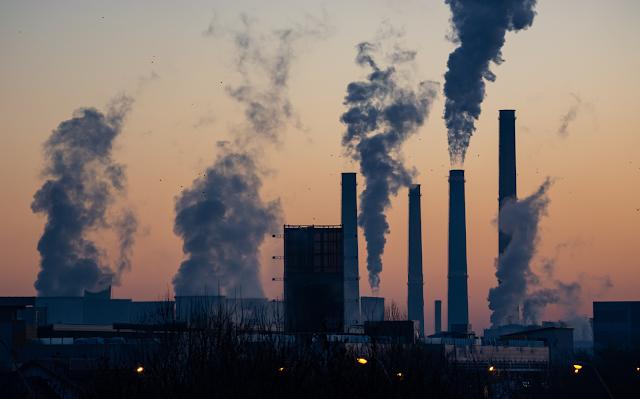 A imagem mostra uma foto de uma indústria liberando no ar gases poluentes. A foto foi tirada no crepúsculo e está quase escura. A fumaça é cinza e preta.