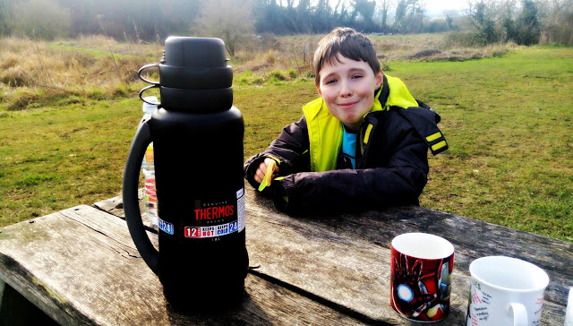 `Thermos flask on a picnic bench with mugs and a hungry-looking boy.