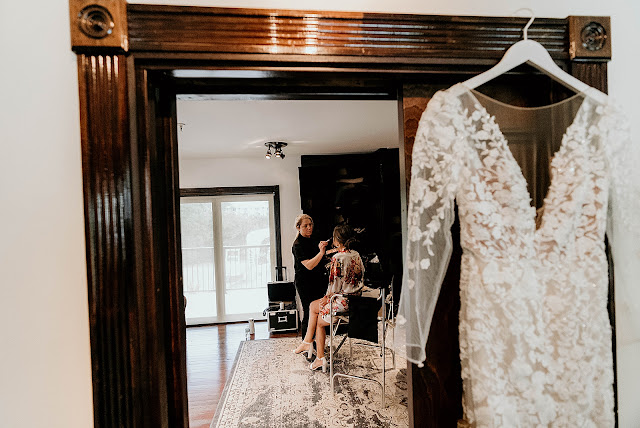 Mirror showing Bride getting ready makeup artist doing makeup and wedding dress on coat hanger The Manor on St Lucie Crescent Wedding captured by Stuart Wedding Photographer Heather Houghton Photography