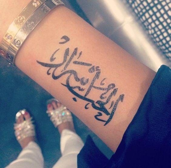 antebrazo de una bella señorita lleva un tatuaje arabe que dice el amor son secretos