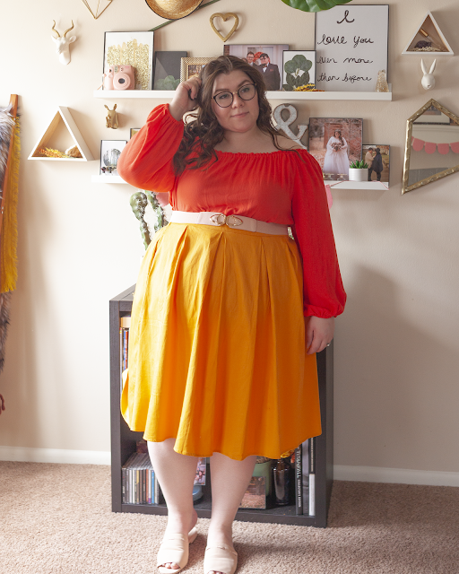 An outfit consisting of a coral off the shoulder dress worn as a top under a yellow midi skirt and pink slide sandals.