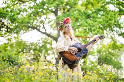 Sofia Talvik med midsommarkrans och gitarr i grönska