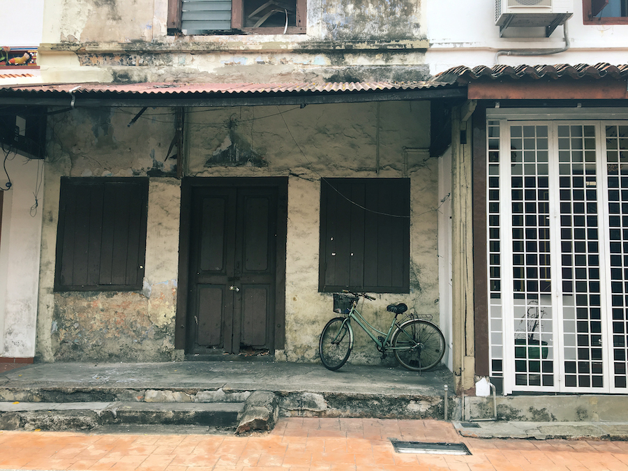 A crumbling facade with a bicycle in Malacca