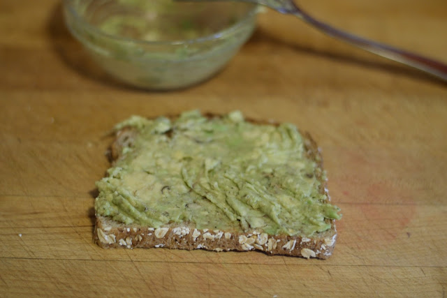 The mashed avocado smeared over the honey oat bread toast.