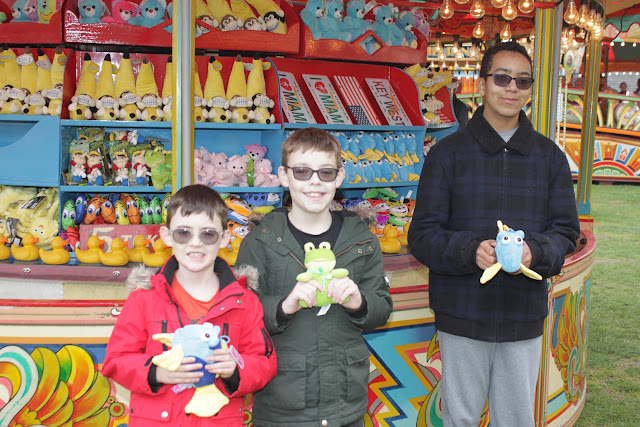 Two of my nephews and my son show off their hook a duck prizes.