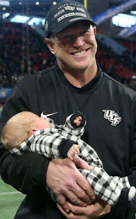 Ashley Neidhardt's husband Scott Frost carrying their baby boy