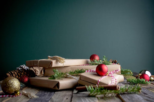 Pile of christmas gift art prints wrapped in brown paper among Christmas decorations