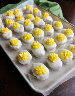baking tray lined with wax paper and covered in rows of deviled egg cake balls