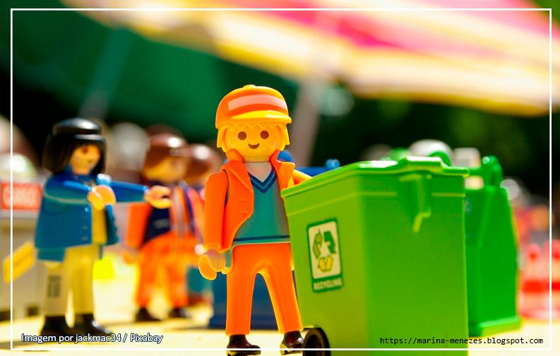 a imagem mostra vários bonecos de playmobil  em um campo. No primeiro plano, um boneco com roupas laranjas e boné da mesma cor, empurra um carrinho verde, com o símbolo de reciclagem estampado nele. Ao fundo, vários bonecos da playmobil diferentes aparecem desfocados