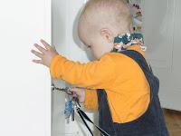 Baby versucht Schlüssel in ein Schlüsselloch zu stecken