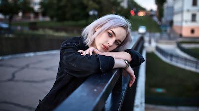 Chica joven con pelo blanco apoyada en una barandilla en el parque