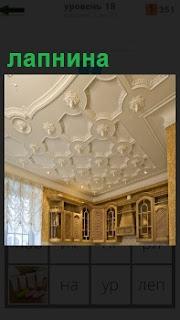 Потолок в комнате сделана лепнина по всему периметру разнообразная