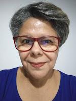 Mulher, de cabelos grisalhos, usando óculos de armação vermelha