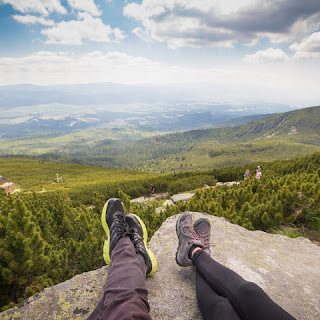couple resting atop mountain on a rock overlooking scenic pastureland
