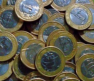 A imagem mostra muitas moedas que simbolizam o lucro excessivos dos banqueiros do Brasil e do mundo sobre a população explorada até nas filas.