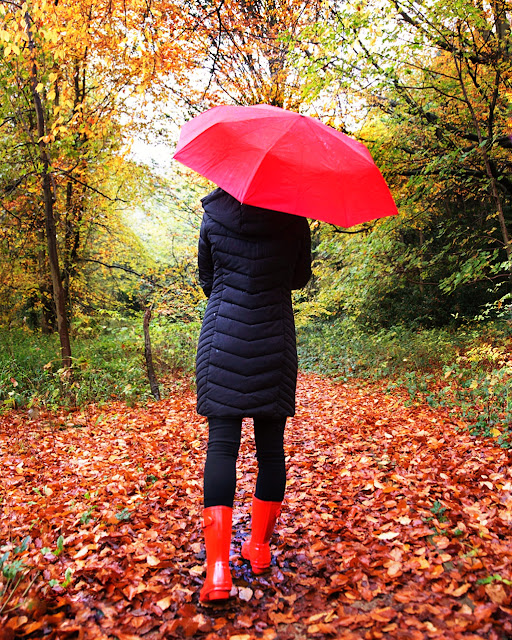back of woman wearing red wellies with red umbrella