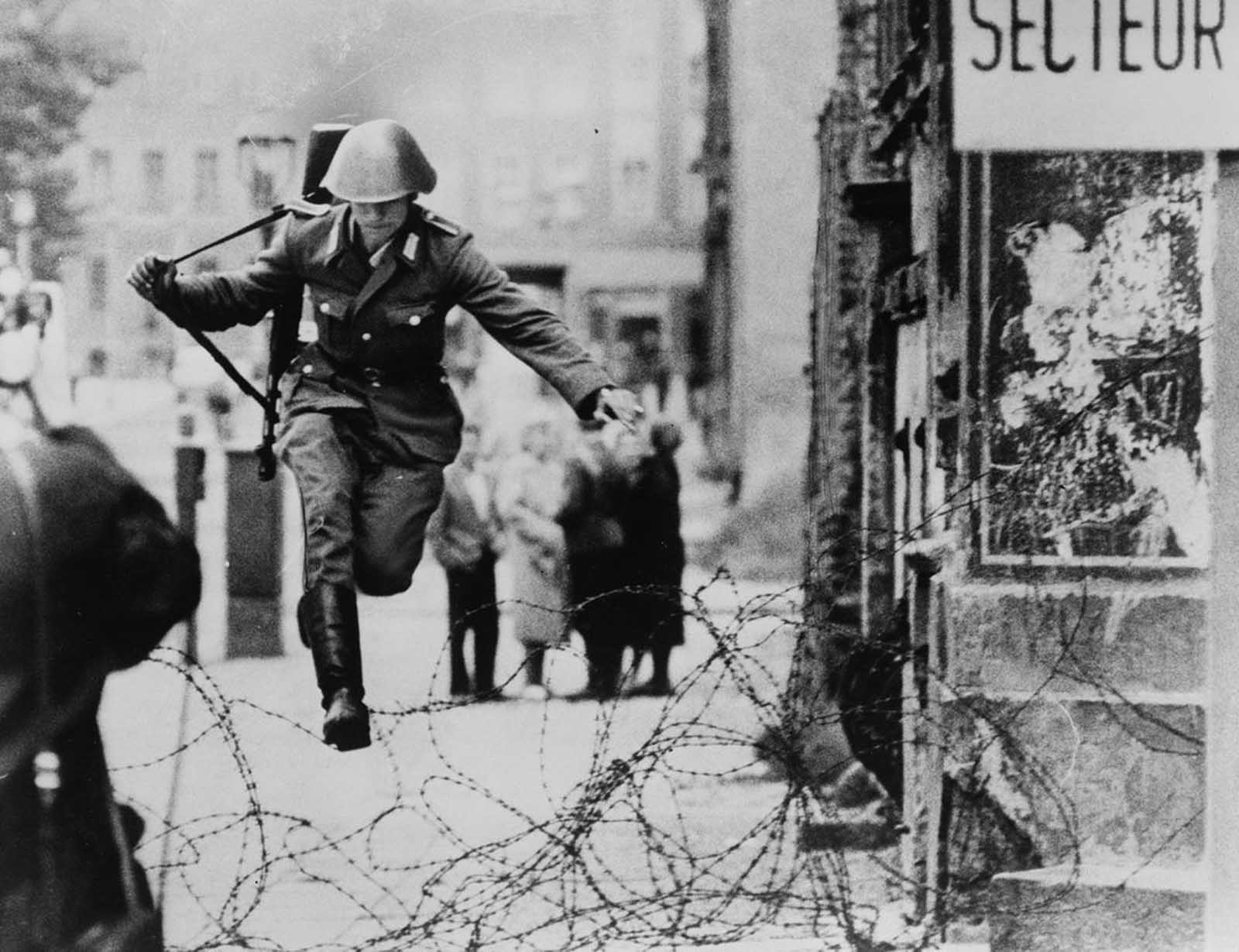 East German border guard Conrad Schumann leaps into the French Sector of West Berlin over barbed wire on August 15, 1961. More info about this picture.