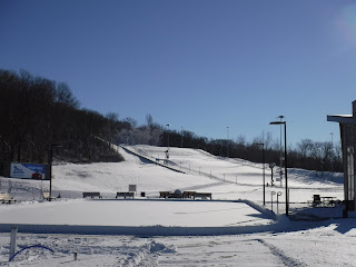 a snowy hill for sledding is visible behind a snow covered ice skating rink at Cone Park in Sioux City, Iowa