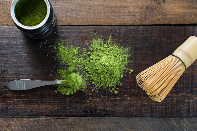 The image has green matcha powder which is lying on a wooden workbench