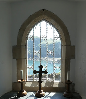 View of sea and cliffs through chapel window