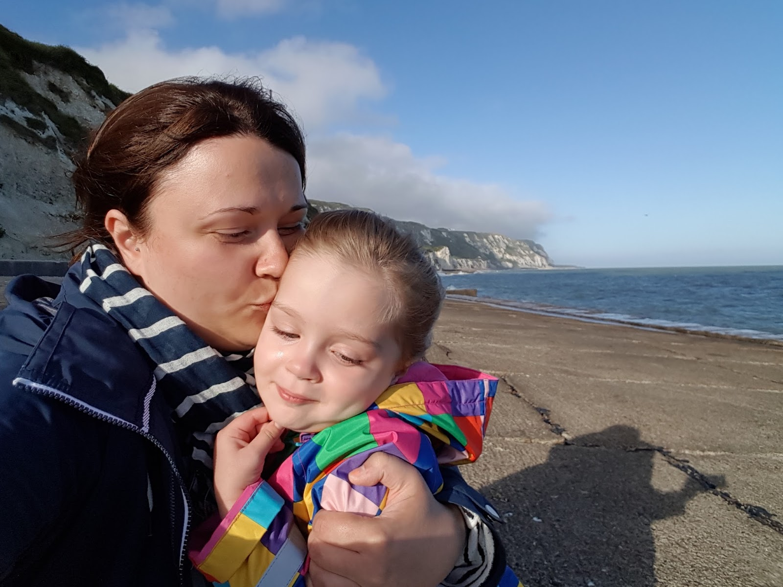 mum giving daughter a kiss on the beach