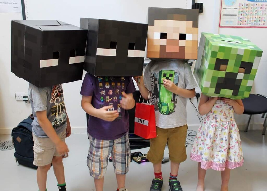Some children who love Minecraft wearing Minecraft style boxes on their head