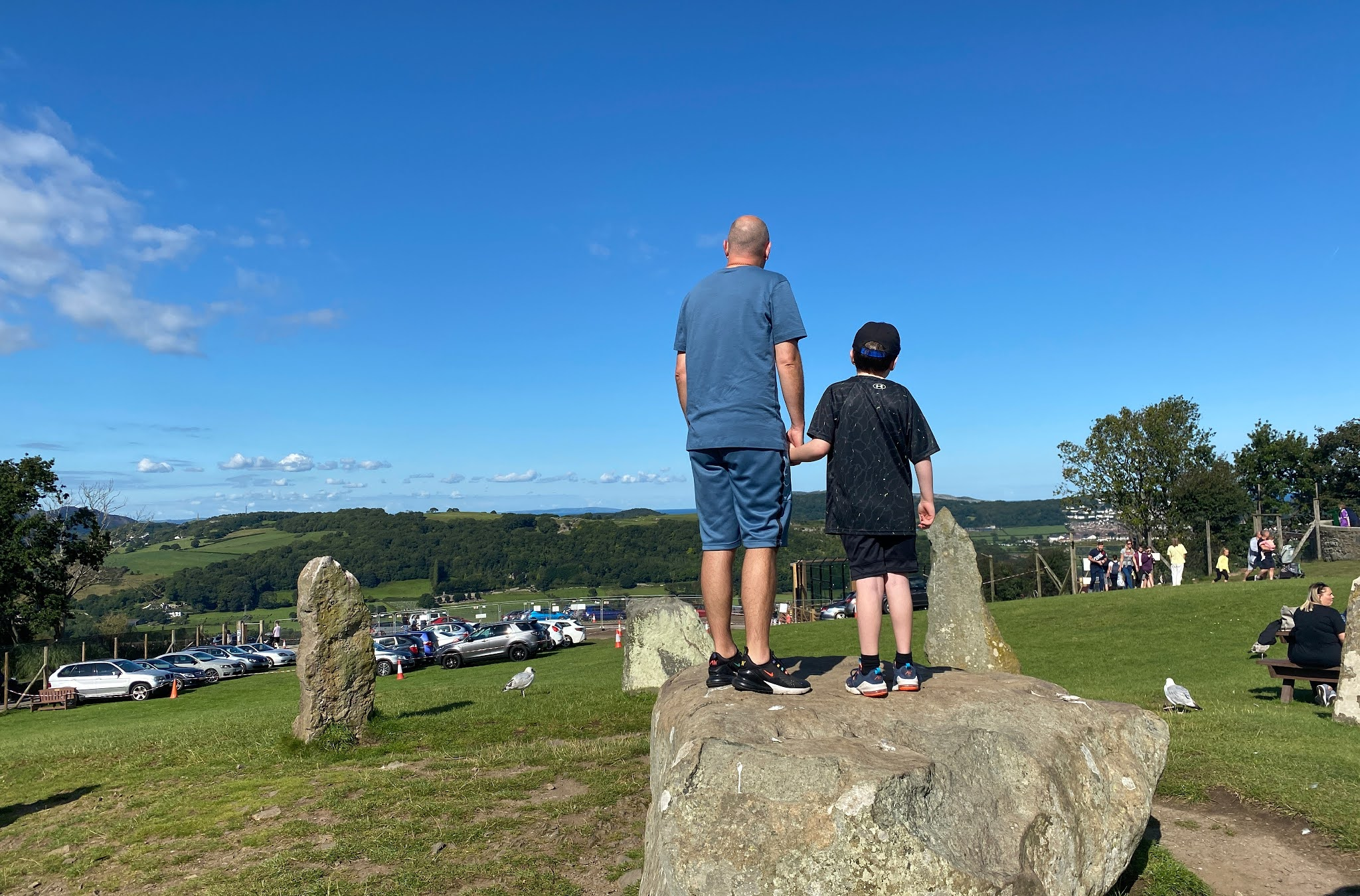Dad and son standing on a large rock