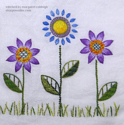 Three embroidered flowers complete on flour sack towels