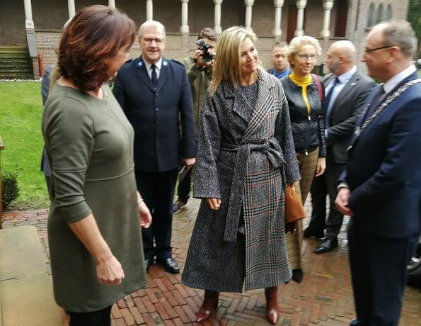 Queen Maxima wore a new mixed-check belted coat by Oscar de la Renta, and carries Uterque bag. Creolen gold earrings, Cartier smartwatch