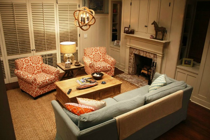 Grace and Frankie living room in beach house living room with fireplace and blue sofa.